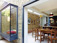 View from terrace into open-plan kitchen with bay window in brick façade and window seat
