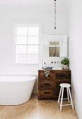 Vintage Waschtischmöbel aus rustikalem Holz in Badezimmerecke neben freistehender weißer Badewanne