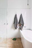 Freistehende Badewanne in bodenebenem Duschbereich mit schwarz-weiß gestreiften Handtüchern an weiß gefliester Wand
