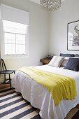 Gelbe Tagesdecke auf Doppelbett in schlichtem Schlafzimmer
