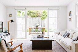 Wohnzimmer mit kastenförmigem Couchtisch und hellem Sofa vor offenen Terrassentüren und Blick auf Essplatz im Freien