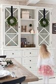 Girl walking past white kitchen dresser decorated with wreaths of box leaves