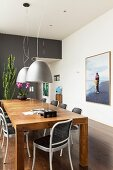 Chairs around solid wooden table below grey pendant lamps