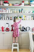 Girl on step stool in front of kitchen counter and open shelf full of storage containers