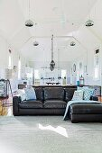 Black leather couch in open, former church room under pendant lights, dining area in background