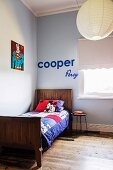 Colorful patchwork blanket on wooden bed in light blue room corner, on wall 'Superman' picture and decorative letters