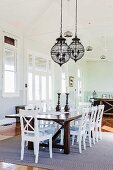 White wooden chairs around wooden table, metal chandelier in the dining area with nostalgic flair
