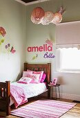 Pink pillows on wooden bed in girl's room, decorative letters on wall, and wall decals with floral motifs