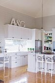 Counter and bar stool in an open fitted kitchen with white, country-style fronts with shiny floorboards