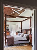 View through open double door into bedroom with canopy bed frame and ceiling fan on wood-clad ceiling