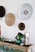Carved ethno console table with decorative objects and wicker plates on the wall
