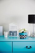 Bouquet of white flowers in fabric cover and desk calendar on turquoise chest of drawers