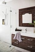 Vanity unit with modern drawer base cabinet, wall mirror with carved frame and glazed, floor-level shower area