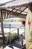 Wooden jetty with thatched roof and surfboard ajar, pool view