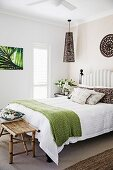 Double bed with upholstered headboard and green bedspread, bamboo bench at the end of the bed
