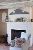 Floral scatter cushion on antique armchair in front of fireplace