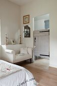White couch against protruding section of wall and rustic door leading to ensuite bathroom