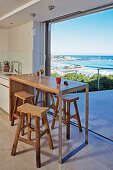Modern wooden counter and rustic bar stools in front of open terrace doors with panoramic sea view