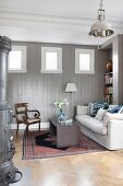 Pale couch and antique chair in wood-panelled room