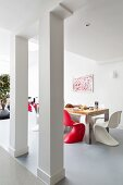 Red and white shell chairs in dining area in open-plan interior