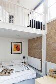 Open-plan bedroom below gallery