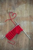 Knitting with red wool: yarn arranged in a love-heart