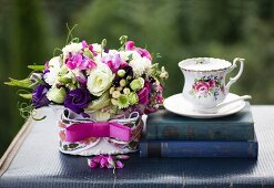 Romantic flower arrangement with pink ribbon next to antiquarian books and vintage-style teacup on vintage case