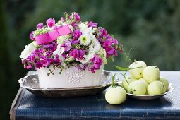 Romantic flower arrangement with apples and silver dish on vintage suitcase outdoors