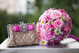 Romantic, pink bridal bouquet next to elegant handbag with sparkling brooch on top of vintage suitcase