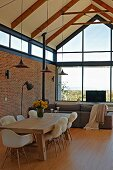 Open-plan interior with exposed wooden structure, brick wall, dining area with classic chairs and solid wooden table