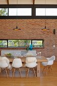 Dining area with classic chairs, solid wooden table and designer lamps in front of brick wall with transom windows in modern interior