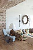 Elegant living area with exposed brickwork in open doorway, antique pale blue armchair and oak parquet floor
