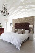 Pale bedroom area with wallpapered partition, dark brown, button-tufted headboard, chandelier and white-painted roof structure