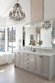 Pale grey bathroom washstand below elegant mirror, chandelier and high, white-painted roof structure