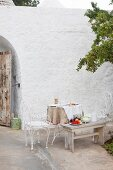 Seating area in courtyard with ornate metal armchairs and table against whitewashed stone façade