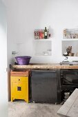 Rustic kitchen counter made from old wooden ladder below niches in wall