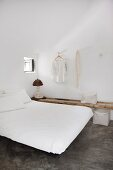 Simple double bed in minimalist bedroom with polished concrete floor