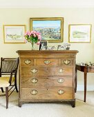Antique chest of drawers with brass handles below framed pictures on wall painted yellow
