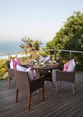 Set round wicker table on wooden deck with view of palm trees and sea