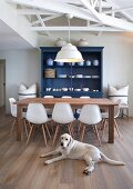 Wooden table, white Eames chairs and blue-painted dresser in renovated country-house interior with Labrador lying on floor