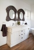White washstand with rustic, ornate, wood-framed mirrors in country-house interior