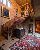 Ornate antique staircase and antique trunk