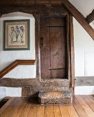 Antique wooden steps leading to rustic, restored wooden door in attic