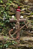 Rusty anchor, metal cross and ornaments against stone wall in garden