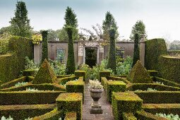 Strictly clipped geometric forms and wall in topiary garden