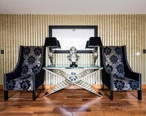 Luxurious armchairs with patterned covers flanking bust and table lamps on extravagant table