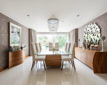 Glass-topped dining table on exotic-wood base and upholstered chairs in elegant dining room with glossy tiled floor