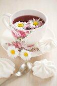 Daisies floating in tea in floral teacup