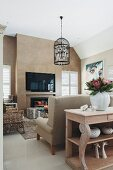 Wooden console table against back of sofa, pendant lamp with bird-cage lampshade and flatscreen TV in lounge