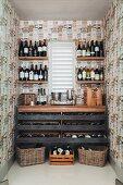 Wine store below and flanking window in custom-built wine racks in narrow room